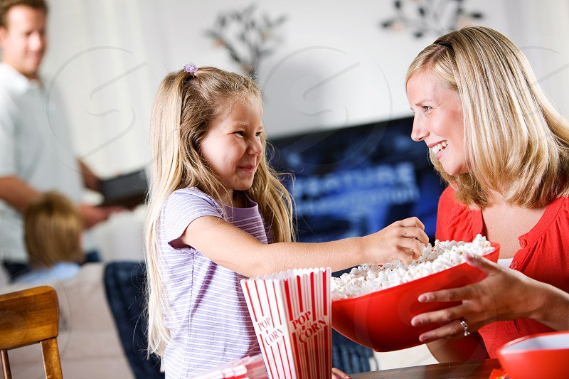 Girl helps mom with popcorn during movie night.  movie movie night television family parent child helping popcorn bowl snack  photo