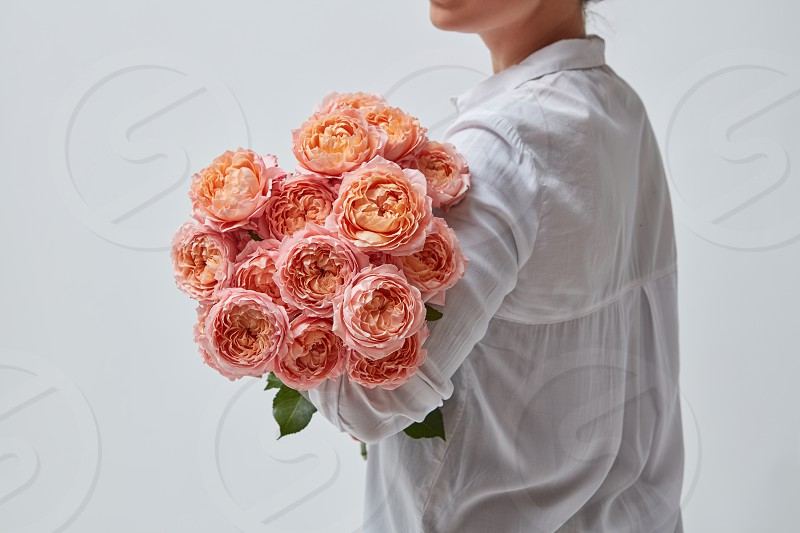 A very beautiful bouquet of pink roses is held by a woman. the best gift for a girl in Valentine's Day. photo