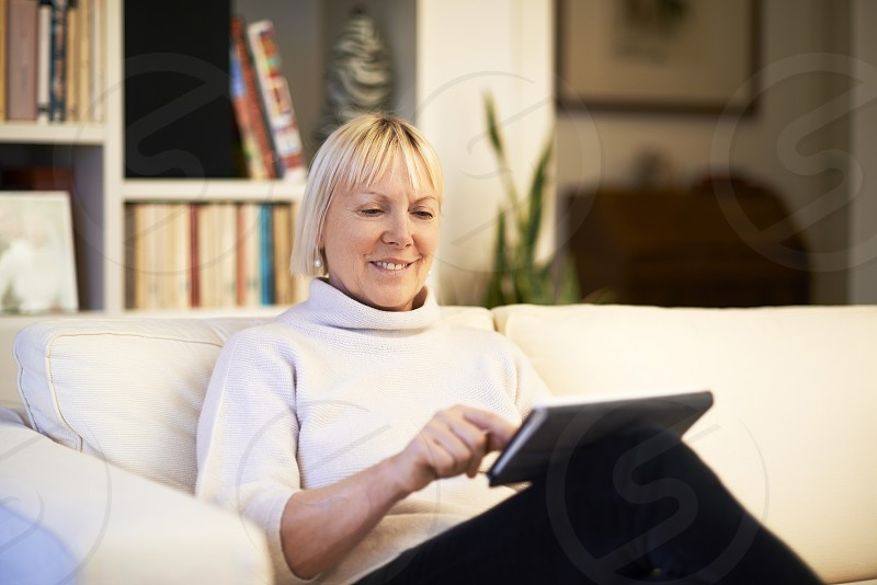 sofa; senior; woman; home; web; ipad; smile; 60s; adult; beautiful; blonde; browsing; casual; caucasian; cheerful; communication; computer; couch; digital; display; elderly; email; enjoy; female; finger; gesture; gesturing; hand; hands; happy; indoors; internet; laptop; lifestyle; mail; monitor; multitouch; one; people; person; portrait; reading; relax; sitting; smiling; tablet; technology; touch; touching; wi-fi photo