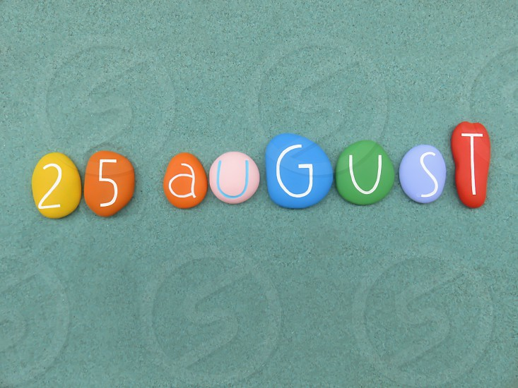 25 August calendar date composed with multi colored stonen over green sand                             photo