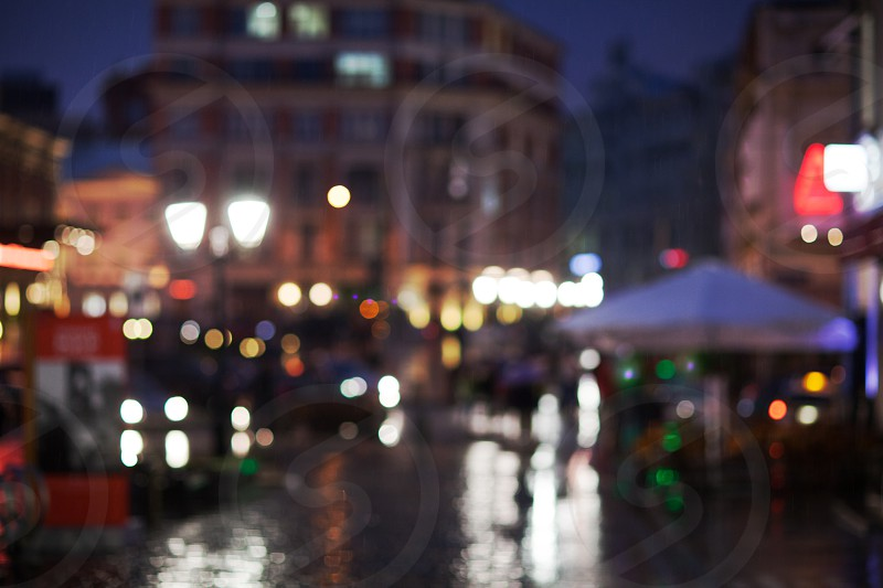 Blurred shot of rainy evening in the city. Street and lanterns lights reflecting on wet road photo
