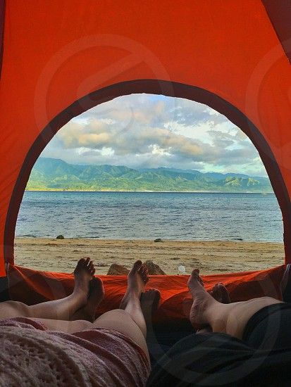 3 person laying in dome tent facing beach and mountains under cloudy sky photo