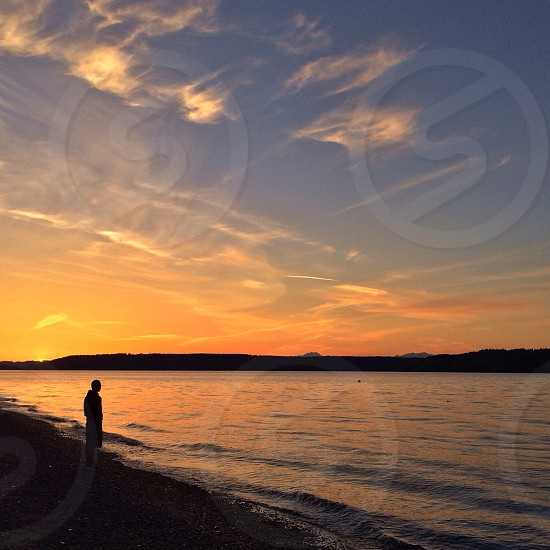 view of man beside sea during sunset photo