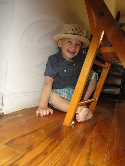 boy wearing gray collared shirt and straw hat under chair photo