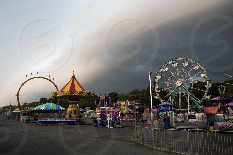 Empty fair or festival midway with amusement rides coaster loop Ferris Wheel swings and ticket booth with looming clouds overhead photo