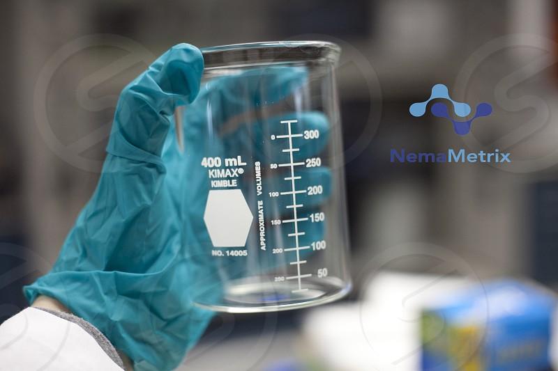 person holding laboratory Nema Metric glass canister photo