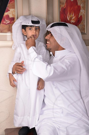 man and boy wearing white thobes photo