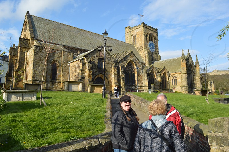 Lady laughing in conversation with two others in front of historic English church building in Scarborough United Kingdom photo