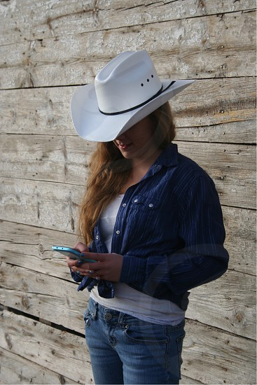 Cowgirls Cowboy boots cowboy hat western rustic barn work white work to be done break cell phones  photo