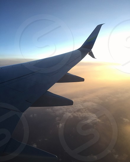right wing of an air plain with clouds beneath it during golden hours photo