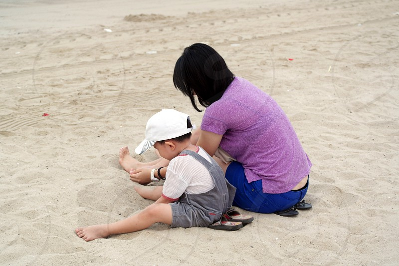 mother and son sitting on a gray beach sand during day time photo