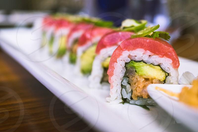 sliced sushi roll served on white ceramic rectangular plate photo