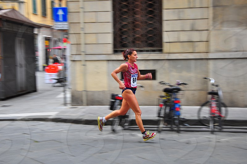 woman in red white and yellow running shoes running on grey concrete road photo