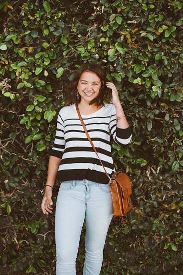 woman with brown leather satchel standing by the hedge photo