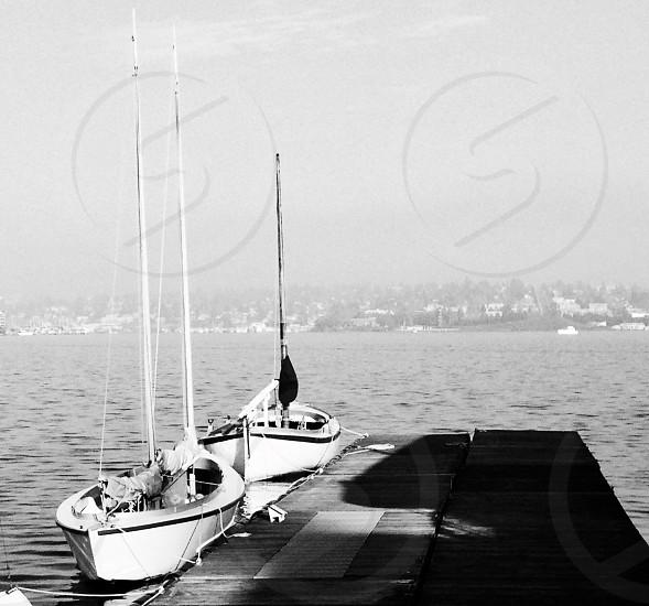 BLack and white photo two sailboats pierside photo