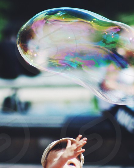 child reaching up to a bubble photo