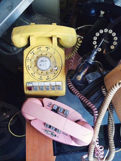 beige rotary phone beside pink push button phone photo