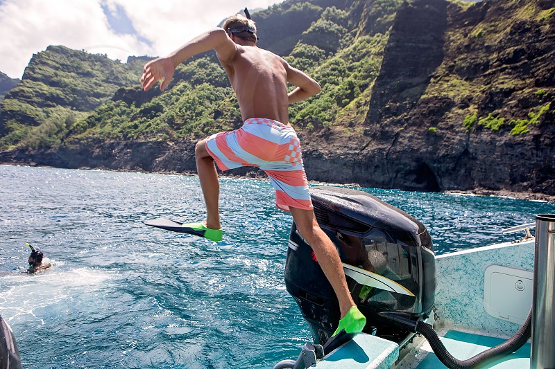 Snorkeling on the Napali Coast Kauai Hawaii Young man jumping off the boat photo