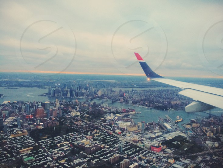 aerial view of a river and cities with lots of buildings and white left wing of airliner under grey cloudy sky during daytime photo