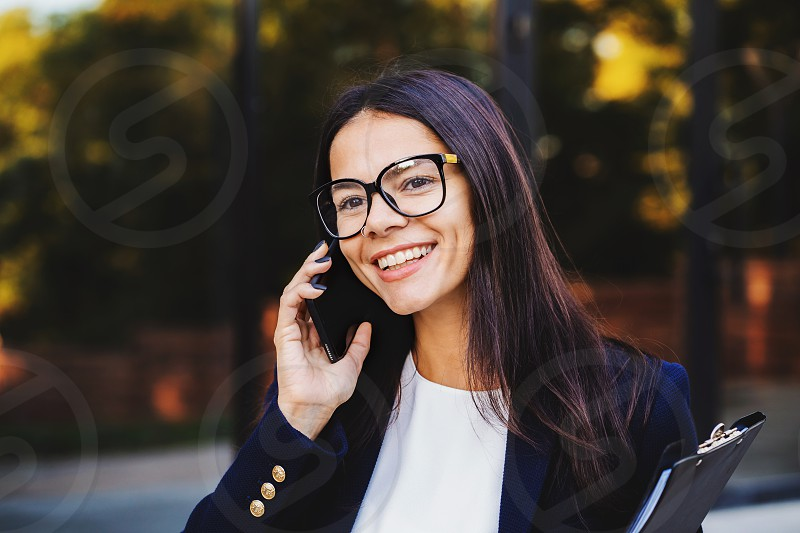 Beautiful mixed race young woman listening to music on headphones with smartphone. Hispanic hipster girl dancing to rhythm and singing along melody in the park photo