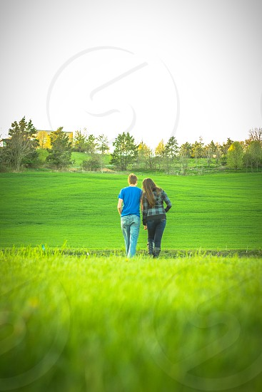 man wearing blue t-shirt and blue denim jeans near woman wearing black and blue jacket and blue denim fitted jeans walking towards green grass field at daytime photo