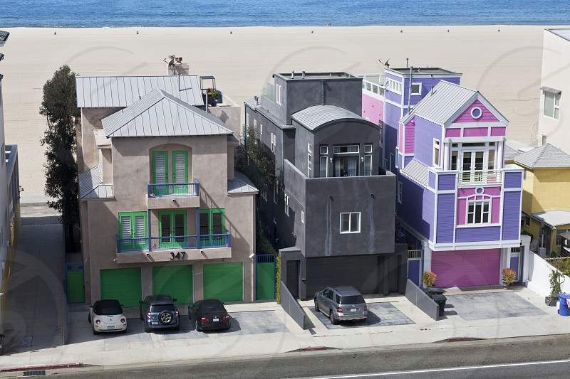 beach row homes with cars parked in driveways with blue water in the distance photo