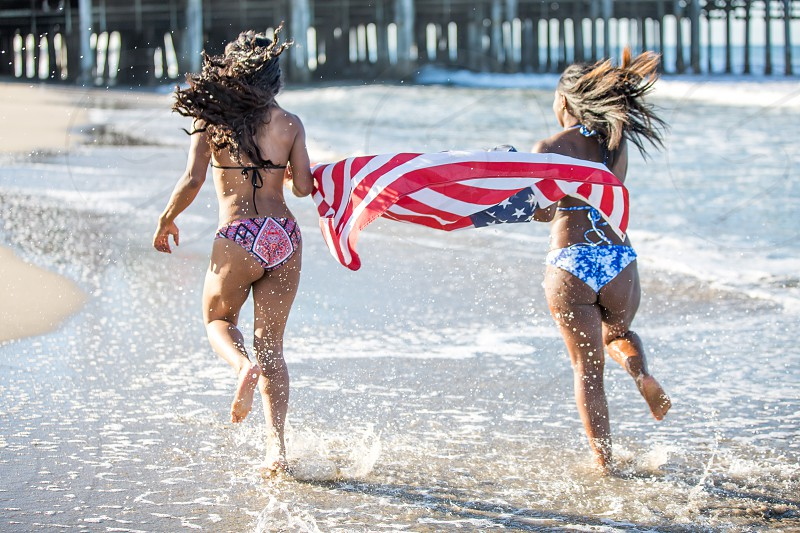 African American Women running on the beach with American Flag Celebrating the holiday weekend 4th of July Memorial Day photo