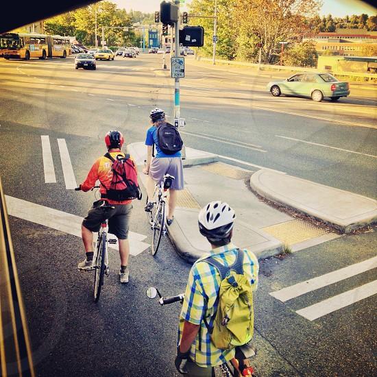 three people on bicycles in helmets crossing street photo