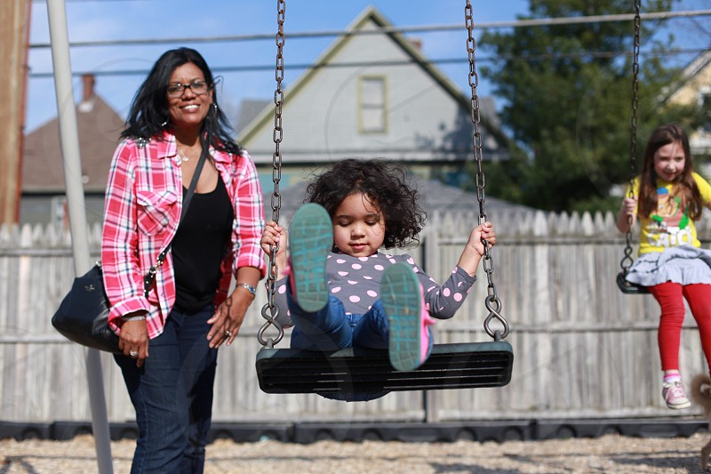 woman smiling pushing a child on a swing with another girl swinging in a park with fence photo