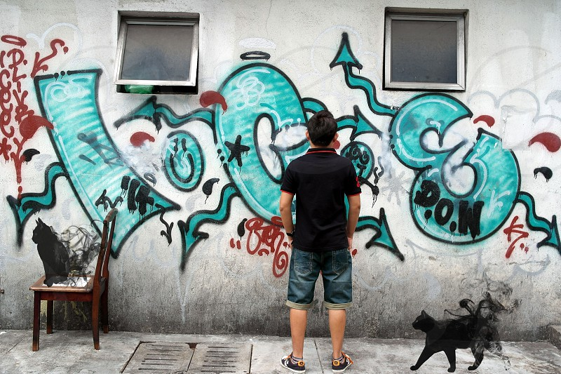 man wearing black polo shirt standing in front of wall with graffiti at daytime photo