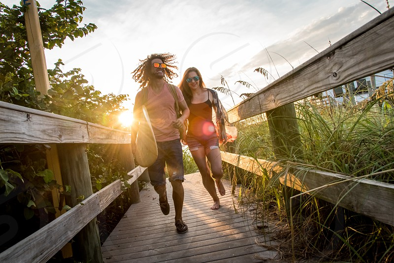 A surfer and a girl run down a boardwalk to the beach during sunrise. photo