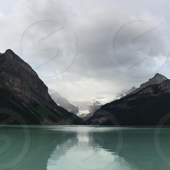 calm blue water lake surrounded by mountain peaks under a grey cloud sky photo
