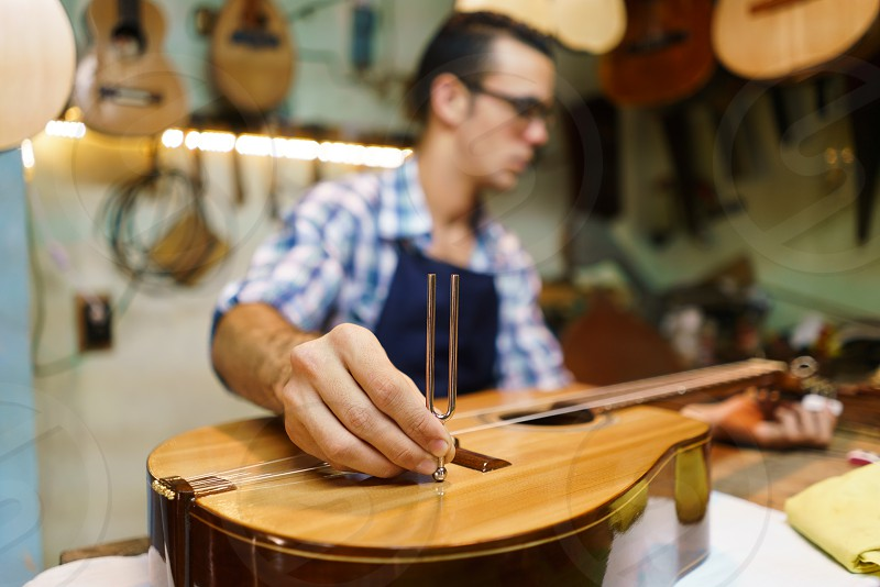 lute; luter; lutemaker; maker; guitar; tuning; string; diapason; tune; tuner; cord; fixing; acoustic; artisan; classical guitar; work; working; shop; acoustic guitar; adult; apron; caucasian; classical; crafts; examining; expertise; focused; handmade; luter shop; man; music; one person; owner; people; precision; preparing; profession; professional; quality; skilled; small business; string instrument; studio; talleur; wood; wooden photo