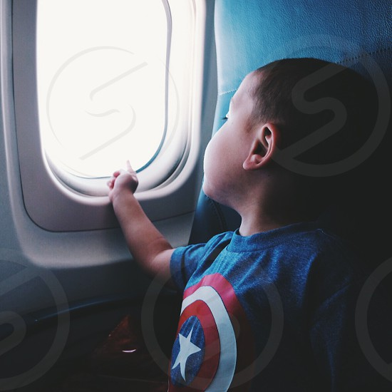 Boy travel airplanes flight window pointing family photo