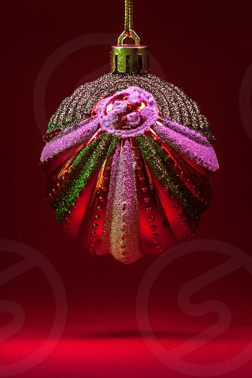 Details of Christmas tree decorated ornaments partially illuminated.  photo