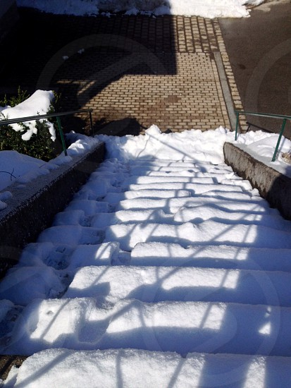gray concrete stairs with green metal railings covered with snow in front of gray pavement photo