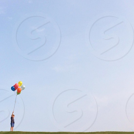 boy holding yellow red blue orange and white balloons photo