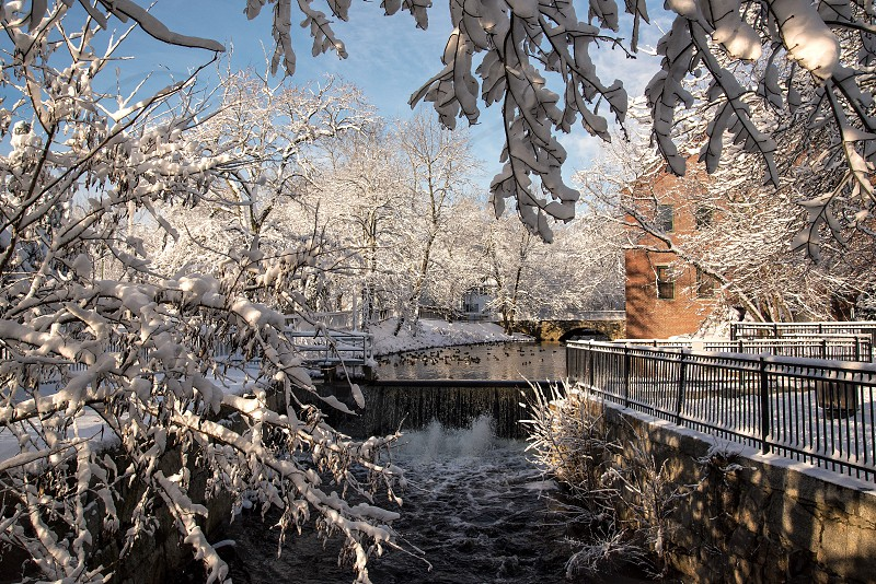 photo of gray steel bannister brown 2 story brick house and a river during winter photo