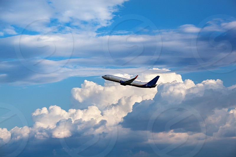 Modern passenger airliner flying in the cloudy sky photo