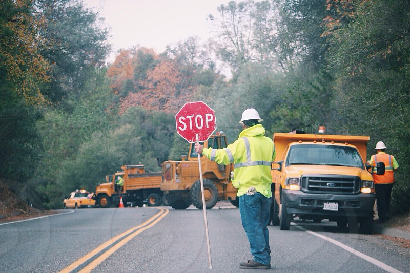 man holding stop sign on road ahead from heavy equipments photo