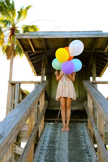Girl holding balloons at beach photo