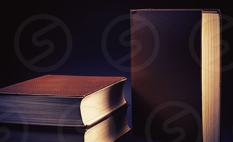 Three old book on blue background.  photo