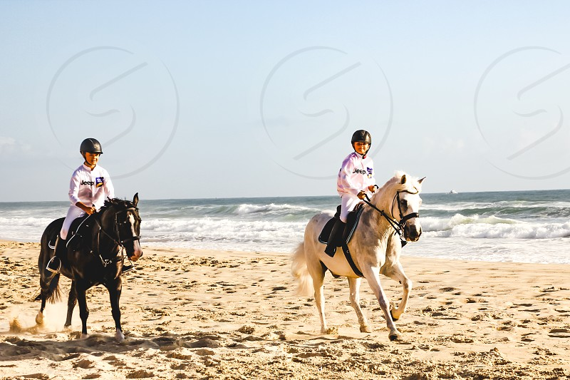 young girls horseback riding at the beach during an equestrian event photo