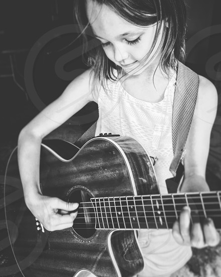 short haired girl in tank top and shorts playing guitar greyscale photography photo
