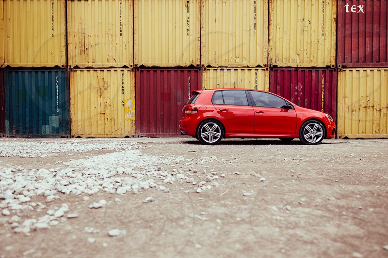 red 5 door hatchback on a brown concrete surface in front of a yellow and red container van photo