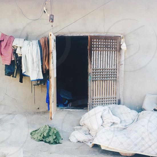 hanged apparels beside opened window door photo