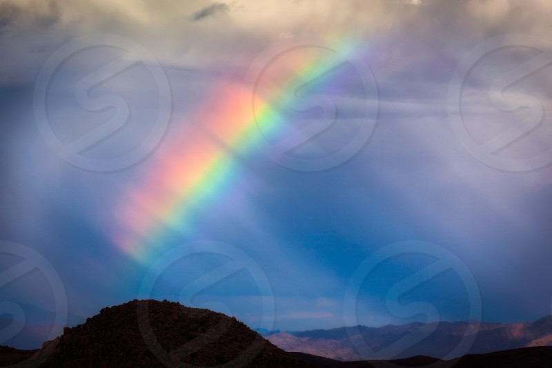 mountain and rainbow photo during cloudy day photo
