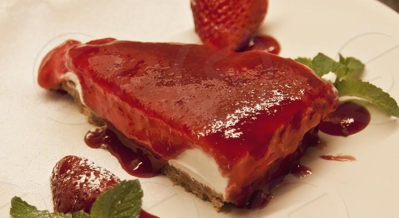 Strawberry cheesecake with sugar coated fresh strawberries and mint leaf garnish photo