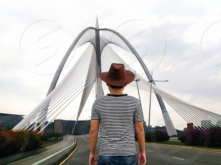 man in gray and black stripe crew neck shirt wearing brown fedora hat standing in front of gray steel tower under gray cloudy sky photo