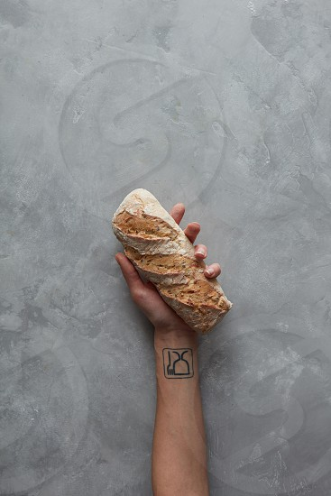 Female holding rustic organic loaf of bread in hands on a gray stone background photo